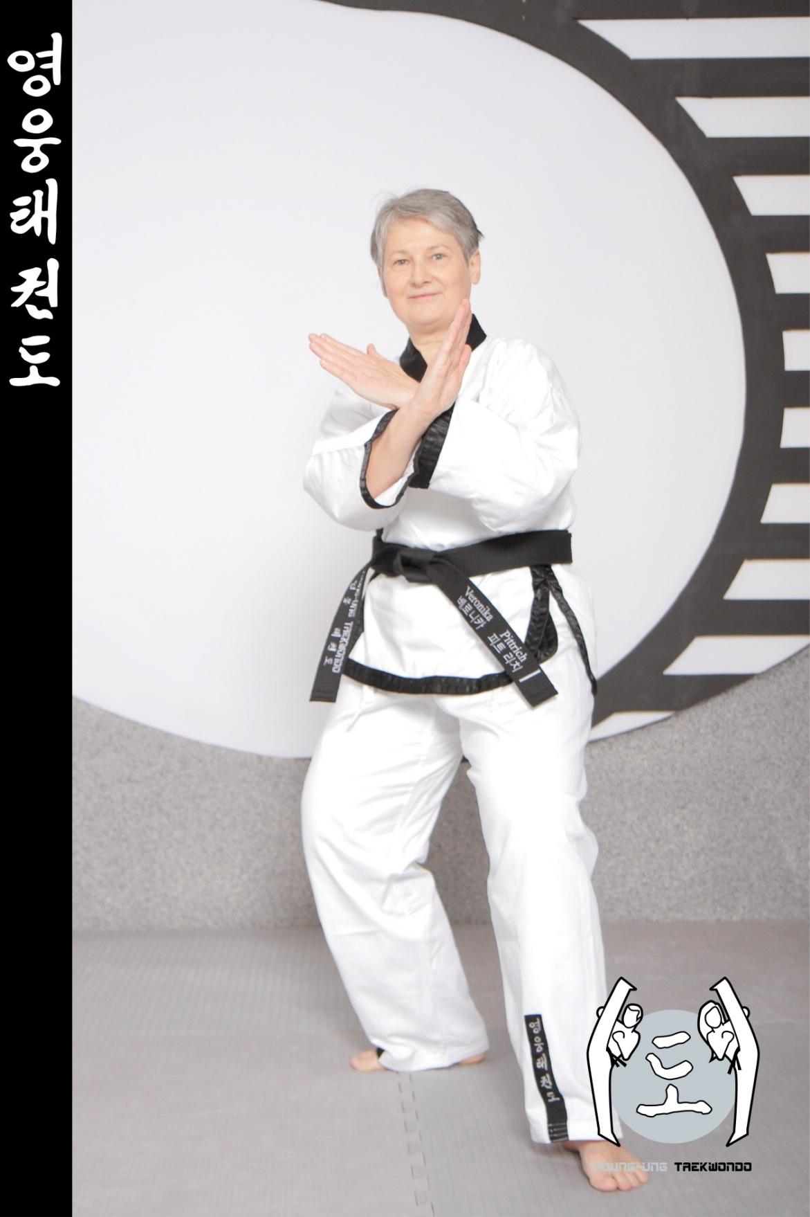 Alte Frau im Taekwondo Kampfanzug mit Schwarzgurt