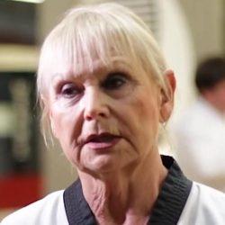 Portrait-Foto einer Seniorin im Kampfanzug als Testimonial für unsere Taekwondo Kurse für Senioren.