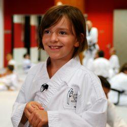 Portrait-Foto eines kleinen Mädchens im Kampfanzug als Testimonial für unsere Taekwondo Erwachsenen Kurse.