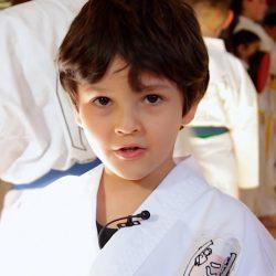 Portrait-Foto eines kleinen Jungen im Kampfanzug als Testimonial für unsere Taekwondo Kurse für Kleinkinder.