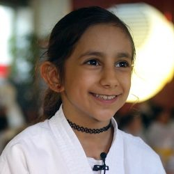 Portrait-Foto eines jungen Mädchens im Kampfanzug als Testimonial für unsere Taekwondo Kurse für Kinder.