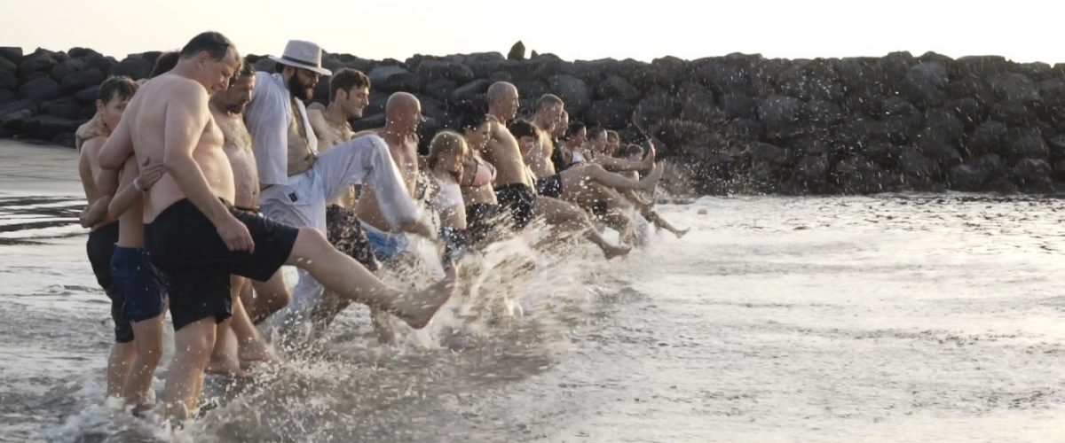 Erwachsene gehen mit großen Schritten ins Meer hinein.