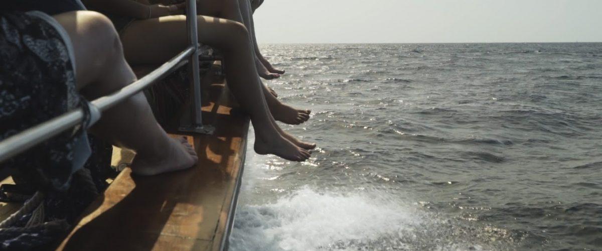 Füsse baumeln vom Schiff ins Meer