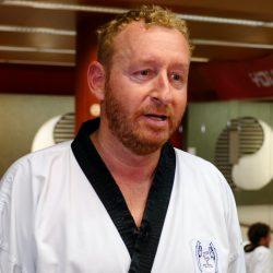Portrait-Foto eines Mannes im Kampfanzug als Testimonial für unsere Taekwondo Erwachsenen Kurse.