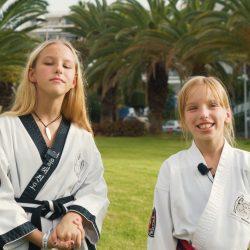 Portrait-Foto zweier junger Mädchen im Kampfanzug als Testimonials für unsere Taekwondo Kurse für Kinder.