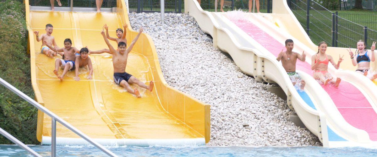 Kinder rutschen eine Wasserrutsche hinunter.